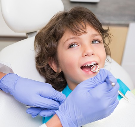 Young person smiling at dentist during children's dentistry exam