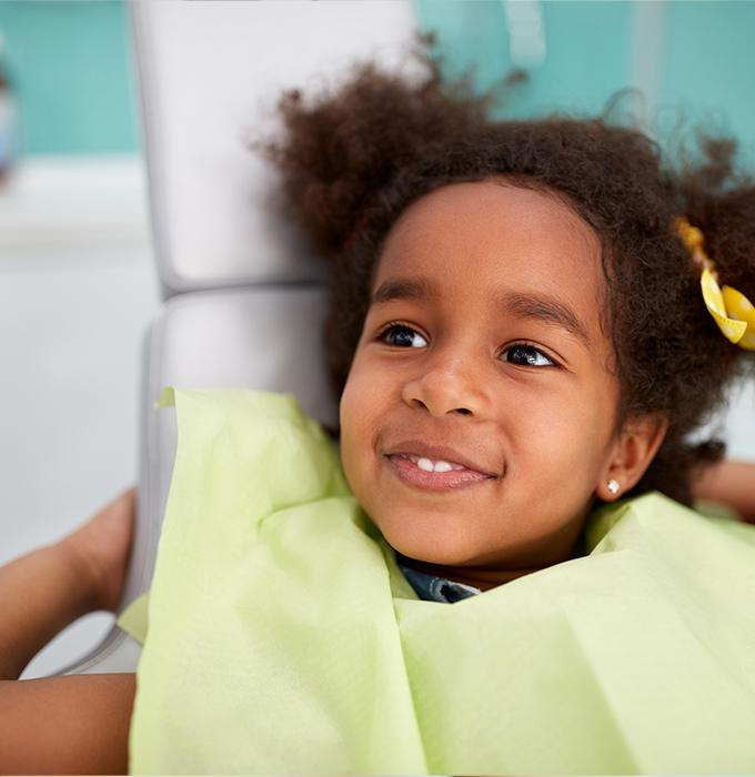 Child in dental chair smiling during first visit