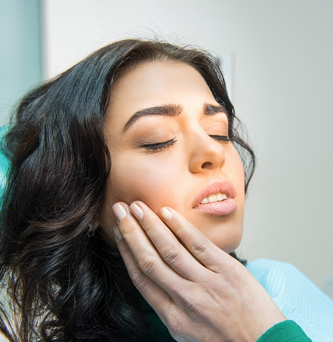 Woman holding jaw during emergency dentistry treatment